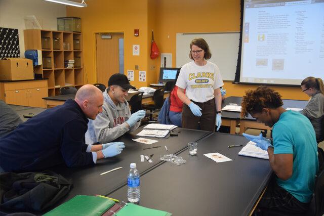 A biology professor works with Clarke University undergrad biology major students