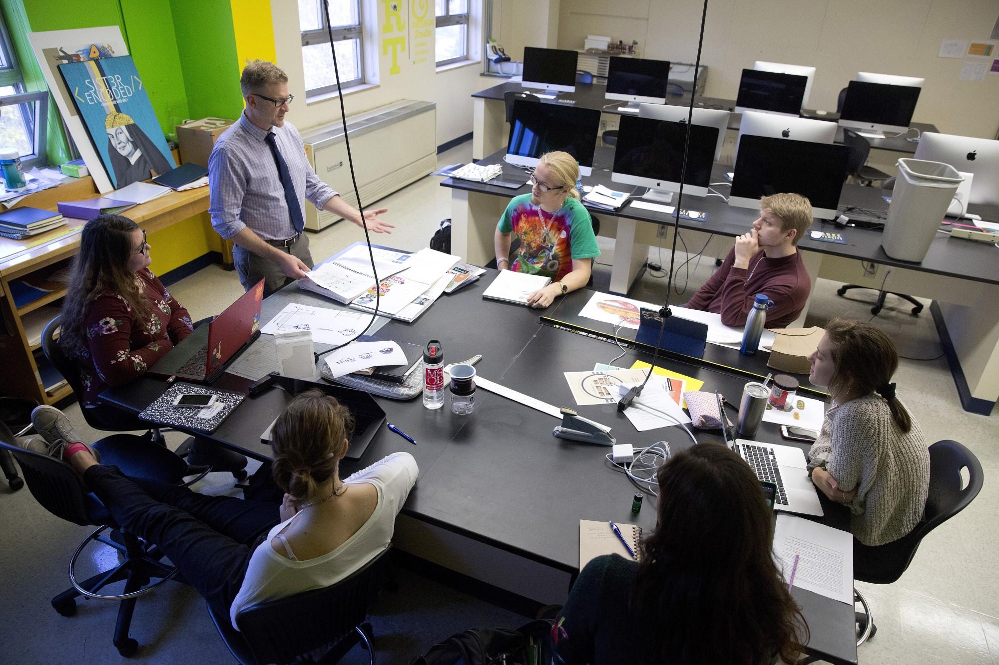 Clarke University Graphic Design Major students in class receiving instruction.