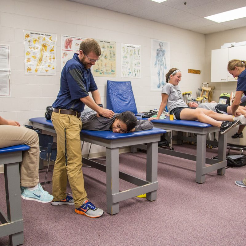 Athletic Training degree students work on each other with feux injuries to practice proper techniques.