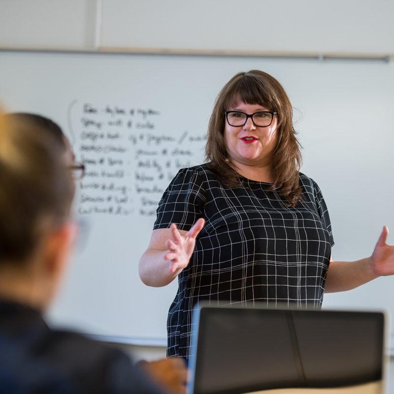 Clarke Professor Emily Goodmann teaching communications Majors in class