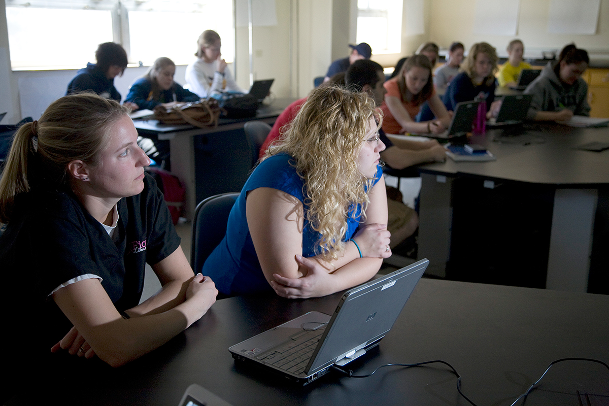 Clarke University students in class listening to lecture by professor.