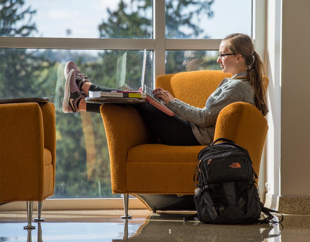 Clarke University Student reading on campus.